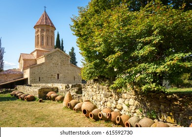Khvtaeba (Holy Spirit) church at Ikalto monastery and ruins of the academy in Kakheti, Republic of Georgia, Caucasus. Old traditional kvevri wine containers in front.