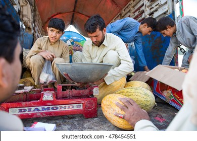 Khyber Agency, PAKISTAN - AUG 09: kid and man sell a fruits in Truck shop in Tirah Khyber Agency, on 09 AUG, 2015 Khyber Agency.