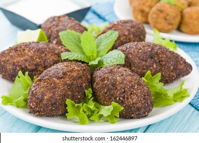 Kibbeh - Middle Eastern minced meat and bulghur wheat fried snack. Also popular party dish in Brazil (kibe). Falafel and tzatziki dip on background.