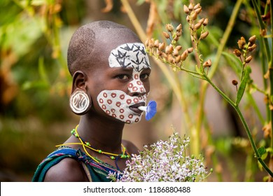 KIBISH, ETHIOPIA - AUGUST 22, 2018: unidentified woman from Surmi tribe, with flower decorations. Surmi are also called Suri or Surma and live in villages in the south-western part of Ethiopia