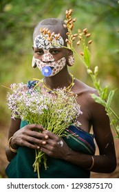 KIBISH, ETHIOPIA - AUGUST 22, 2018: unidentified woman from Surmi tribe, with  painted face and natural decorations of leave and flowers in a wreath. Surmi are also called Suri or Surma