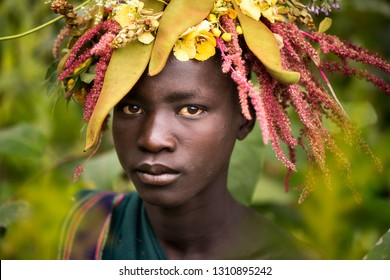 KIBISH, ETHIOPIA - AUGUST 22, 2018: unidentified young man from Surmi tribe, with  natural decorations of leave and flowers. Surmi are also called Suri or Surma