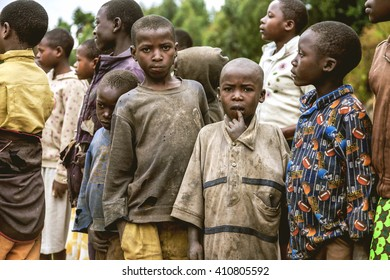 KIBUYE, RWANDA, AFRICA - SEPTEMBER 11, 2015:Unknown the African children. Two of them look into camera, the others look another sides. All clothes of them are torn and dirty.