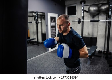 Kick boxing training. A dedicated man wears boxing gloves in an indoor modern gym with equipment. The man in sports and boxing is just getting ready to punch