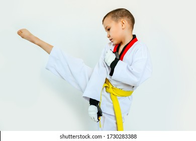kick a boy athlete with a yellow belt on a white background