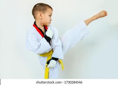 kick a boy athlete with a yellow belt from the side on a white background