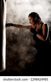 kick fighter girl punching a boxing bag