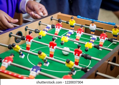 Kick off strike in table football game. Young people playing foosball table game.