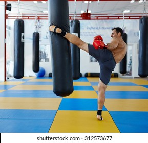 Kickbox fighter training in the gym with the punch bag
