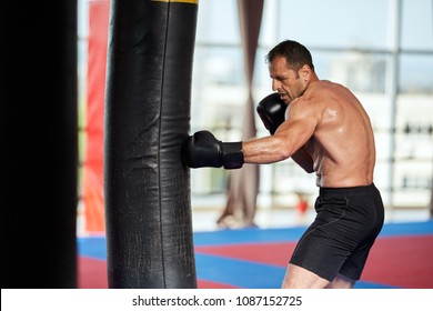 Kickbox fighter training with heavy bag in the gym