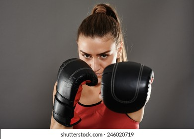 Kickbox girl delivering a left jab, studio shot