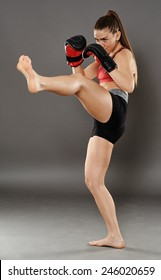 Kickbox young woman delivering a kick, over gray background