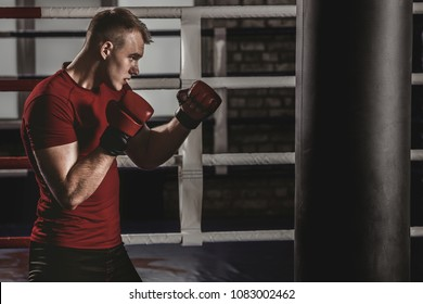 Kickboxer exercises blows on the pear in the gym. Mixed figher trains in the oldschool gym.