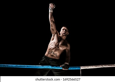 Kickboxer posing in the ring. The athlete climbed the ropes and took a winning pose. The concept of mma, wrestling, muay thai. Mixed media