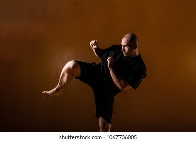 A kickboxer practicing a high kick in a indoor dojo.