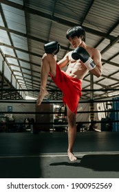 Kickboxer in the ring do stretches before the fight makes swing movements with his knee