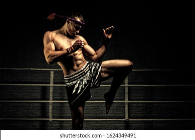 Kickboxer in the ring surrounded by searchlights stretches before the fight. Makes swing movements with his knee. Mongkhon. Mixed media