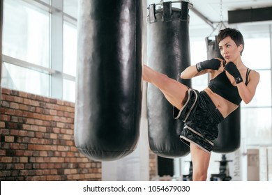 kickboxer in sporty clothers and bandages is throwing punches with legs and arms on workout. striking with leg