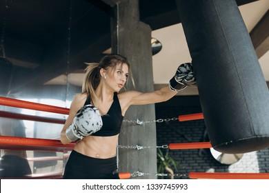 Kickboxer woman athlete training boxing punching bag enjoying intense exercise muslim female kickboxing practice workout in gym