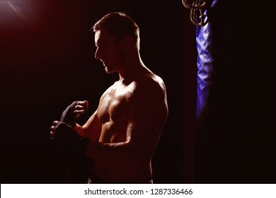 Kickboxing concept. Muscular man prepare for kickboxing. Fit sportsman wrapping up in kickboxing gym. Kickboxing workout. Gloves up.
