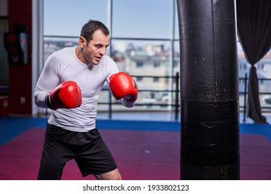 Kickboxing fighter hitting the heavy bag in the gym, training for competition