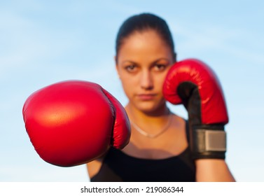 Kickboxing girl exercising in the nature on sunny summer day.
