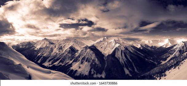 Kicking Horse, Golden, British Columbia, Canada. Beautiful Aerial Panoramic View of Canadian Mountain Landscape during a vibrant sunny and cloudy morning sunrise in winter. Tinted Black and White