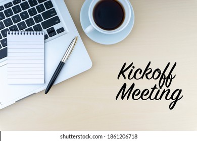 KICKOFF MEETING text with fountain pen, notepad, laptop and cup of coffee on wooden background. Business and copy space concept.
