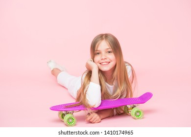 Kid adorable child long hair adore ride penny board. Happy childhood. Ride penny board and do tricks. Girl likes to ride skateboard. Active lifestyle. Girl having fun with penny board pink background.