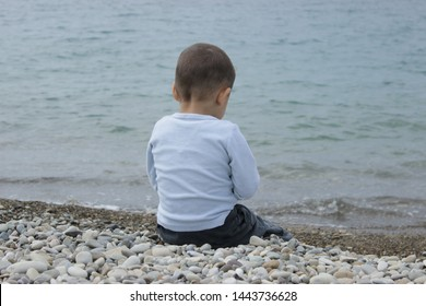 The kid is against the background the blue sea. A lonely child sits on the shore of the Black Sea and He's throwing a stones in the water. The boy ran away from home. The child decided to be alone.