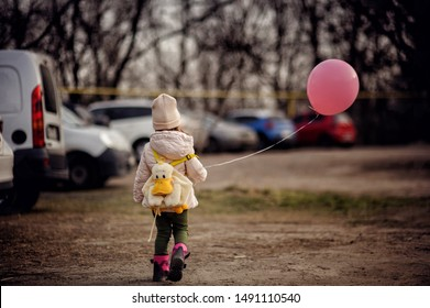 Kid all alone on car parking. Lost child with baloon. Toddler finding parents. Watch the baby.