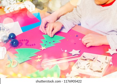 Kid attaches stickers on paper Christmas tree