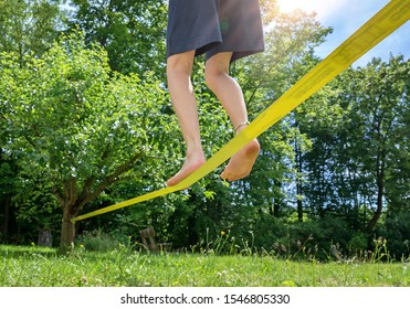 Kid balancing barefooted on a slack line, close up in low angle view