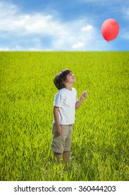 Kid with balloon standing on beautiful meadow