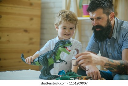 Kid and bearded man play fight between kid's toys on the wood table, different dinosaurs. Educating process while playing games with children. Development concept. Home zoo game. Play time