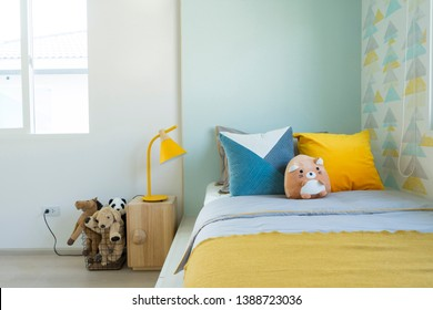 Kid bedroom in blue and yellow tone pillow with many doll on bed.