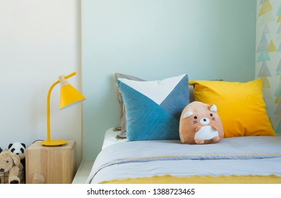 Kid bedroom in blue and yellow tone pillow with many doll and yellow table lamp.