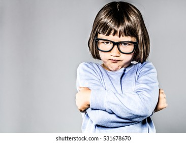 kid body language with sulking, pouting small child crossing her arms expressing attitude, anger and frustration, contrast effects, copy space