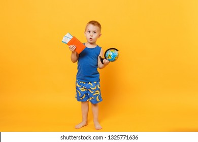 Kid boy 3-4 years old in blue beach summer clothes hold globe passport isolated on bright yellow orange wall background children studio portrait. People childhood lifestyle concept Mock up copy space