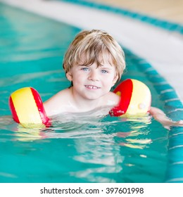Kid boy of 4 years with swimmies learning to swim in an indoor pool. Active and fit leisure for children.