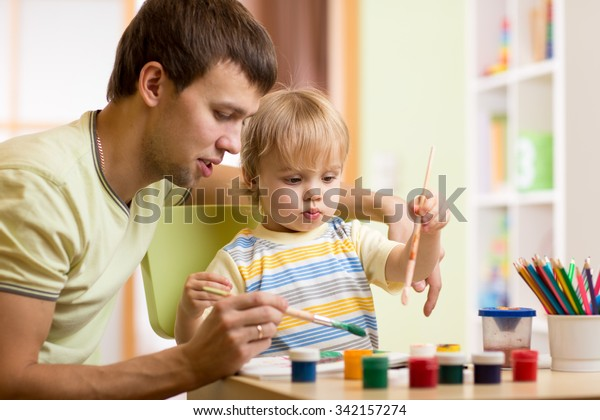 kid boy and daddy painting together in nursery