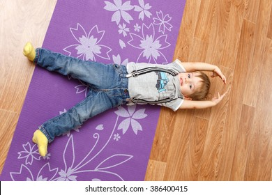 Kid boy doing fitness exercises on the floor