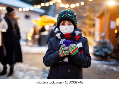 Kid boy drinking hot children punch on German Christmas market. Happy child with medical mask . People with masks as protection against corona virus. Covid pandemic time in Europe and in the world.