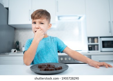 kid boy eating or biting chocolate sweets or candies at modern home kitchen