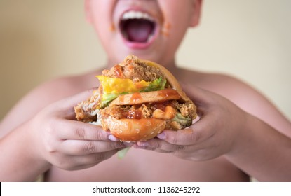 Kid boy eats hamburger in a restaurant and enjoying delicious food