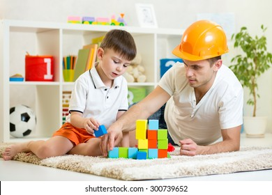 kid boy and father play builders in nursery at home