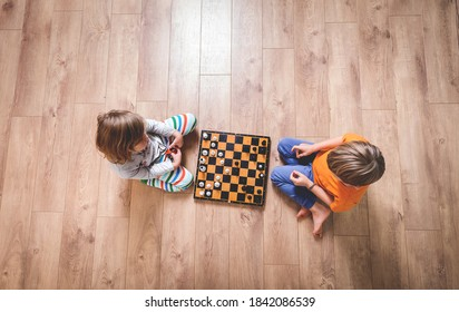 Kid boy and girl playing chess laying on the floor and thinking intensely. Children playing table game. Education at home. School concept