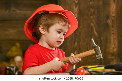 Kid boy hammering nail into wooden board. Child in helmet cute playing as builder or repairer, repairing or handcrafting. Toddler on busy face plays at home in workshop. Handcrafting concept