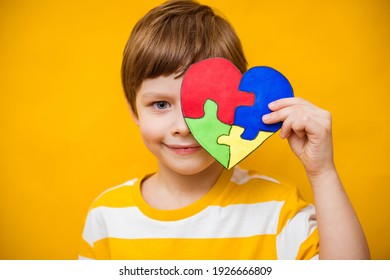Kid boy hands holding puzzle heart, child mental health concept, world autism awareness day, teen autism spectrum disorder awareness concept