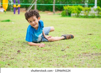 kid boy having fun to play children's playground area at school,kid running and fall down on grass.back to school outdoor activity